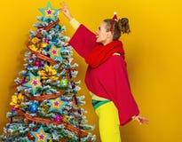 Женщина около рождественской елки на желтой предпосылке украшая стоковая фотография