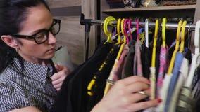 Женщина около шкафа сортируя платья видеоматериал