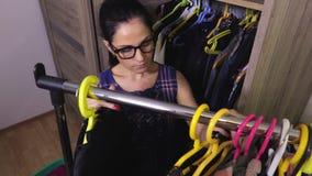 Женщина около шкафа сортируя платья сток-видео