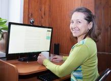 Женщина около домашнего компьютера стоковые изображения