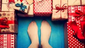 Женщина окруженная к много обернутых винтажных подарков на рождество, точка зрения Стоковые Фотографии RF