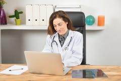 Женщина доктора используя компьтер-книжку в рабочем месте Стоковое Фото