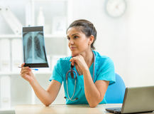 Женщина доктора рассматривая рентгеновский снимок в офисе Стоковая Фотография RF