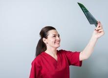 Женщина доктора смотря рентгеновский снимок или рентгеновский снимок Стоковая Фотография RF