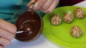 Женщина окунает заготовку popcake в расплавленный шоколад Рядом с плитой другие пробелы сток-видео