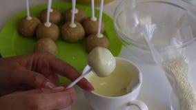 Женщина окунает пробел торта popcake в белый шоколад и брызгает ее равномерно над поверхностью шарика Затем на таблице сток-видео