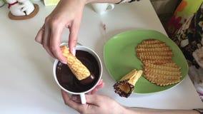 Женщина окунула конус вафли в расплавленный шоколад Ингредиенты для варить сток-видео