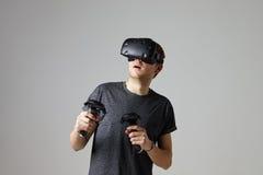 Женщина дома нося шлемофон виртуальной реальности играя игру стоковое фото rf