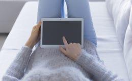 Женщина дома ослабляя чтение на планшете стоковые изображения rf