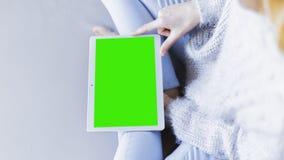 Женщина дома ослабляя чтение на планшете стоковые фото