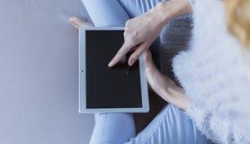 Женщина дома ослабляя чтение на планшете стоковая фотография rf
