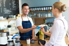 Женщина оплачивая для кофе стоковые изображения rf