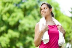 Женщина освежая после бежать на парке города стоковое фото
