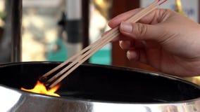 Женщина освещает 3 ручки ладана в открытом огне видеоматериал