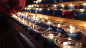 Женщина освещает свечу между другими свечами видеоматериал