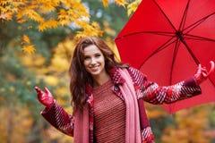 Женщина осени в парке осени с красными зонтиком, шарфом и кожей Стоковое Изображение RF