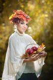 Женщина осени. Красивые творческие состав и прическа в внешнем всходе. Девушка с листьями в волосах держа корзину с яблоками Стоковое Изображение