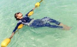 Женщина ослабляет в море бирюзы Стоковое Изображение RF