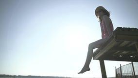 Женщина ослабляет сидеть на краю деревянной молы, ноги отбрасывает около поверхности воды на заднем плане акции видеоматериалы