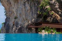 Женщина ослабляя в бассейне безграничности смотря взгляд стоковое фото rf