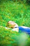 Женщина ослабляя в зеленом поле Стоковые Изображения