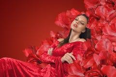 Женщина ослабляя в стуле с большими красными цветками стоковые изображения rf
