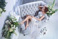 Женщина ослабляя на голубой софе стоковые фото