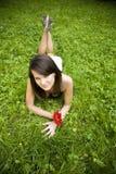 Женщина ослабляя на зеленой траве Стоковое Фото