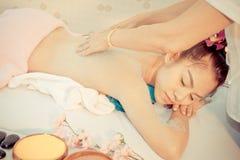 Женщина ослабляя на кровати курорта пока терапевт scrubbing она назад стоковое изображение