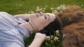 Женщина ослабляя пока слушающ к музыке акции видеоматериалы