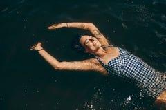 Женщина ослабляя путем плавать в воду стоковые изображения