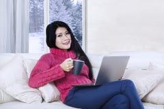 Женщина ослабляя с компьтер-книжкой и горячим чаем Стоковые Фото