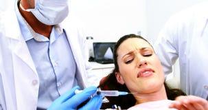Женщина останавливая дантиста для рассматривать ее в клинике акции видеоматериалы