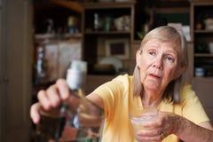 Женщина достигая для бутылки ликера Стоковые Фото