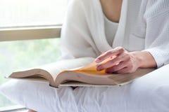 Женщина ослабляет и чтение на кровати с старой книгой Стоковое фото RF
