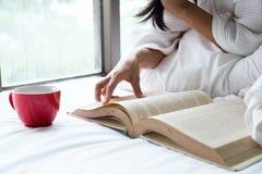 Женщина ослабляет и чтение на кровати с старой книгой Стоковая Фотография