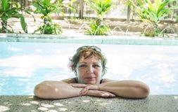 Женщина ослабляя в бассейне в салоне курорта Стоковая Фотография RF