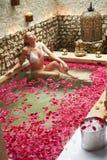 Женщина ослабляя в лепестке цветка покрыла бассейн стоковые фото