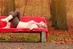Женщина ослабляя в парке падения осени с книгой Стоковое фото RF