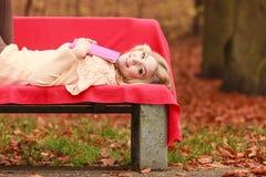 Женщина ослабляя в парке падения осени с книгой Стоковые Фотографии RF