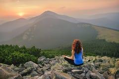 Женщина ослабляя в природе на заходе солнца Стоковая Фотография