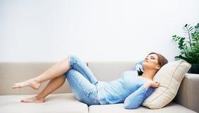 Женщина ослабляя на дому Стоковые Изображения