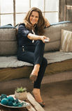 Женщина ослабляя на софе и смотря ТВ в квартире просторной квартиры Стоковое фото RF