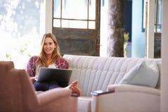 Женщина ослабляя на софе дома используя портативный компьютер Стоковые Фото