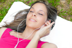 Женщина ослабляя на траве пока слушая музыка стоковые изображения rf