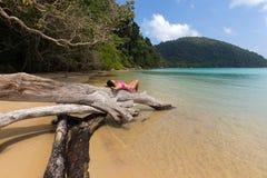 женщина ослабляя на тропическом пляже Стоковое Изображение