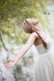 Женщина ослабляя озером Стоковые Фото