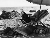 Женщина ослабляя под зонтиком на пляже (все показанные люди более длинные живущие и никакое имущество не существует Гарантии пост стоковые фото