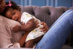 Женщина ослабляя с ее дочерью малыша, урожай средний-раздела Стоковое Изображение