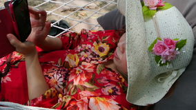 Женщина ослабляя с smartphone на гамаке, полном HD сток-видео